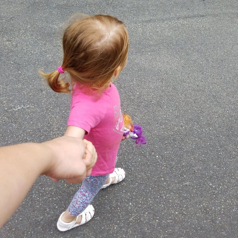 Toddler holding moms hand when running errands