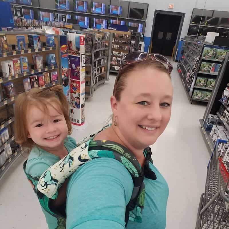 A mom babywearing toddler in a store using a toddler carrier.