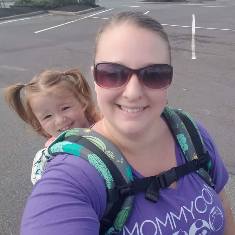 Mom wearing a toddler carrier and a smiling toddler.