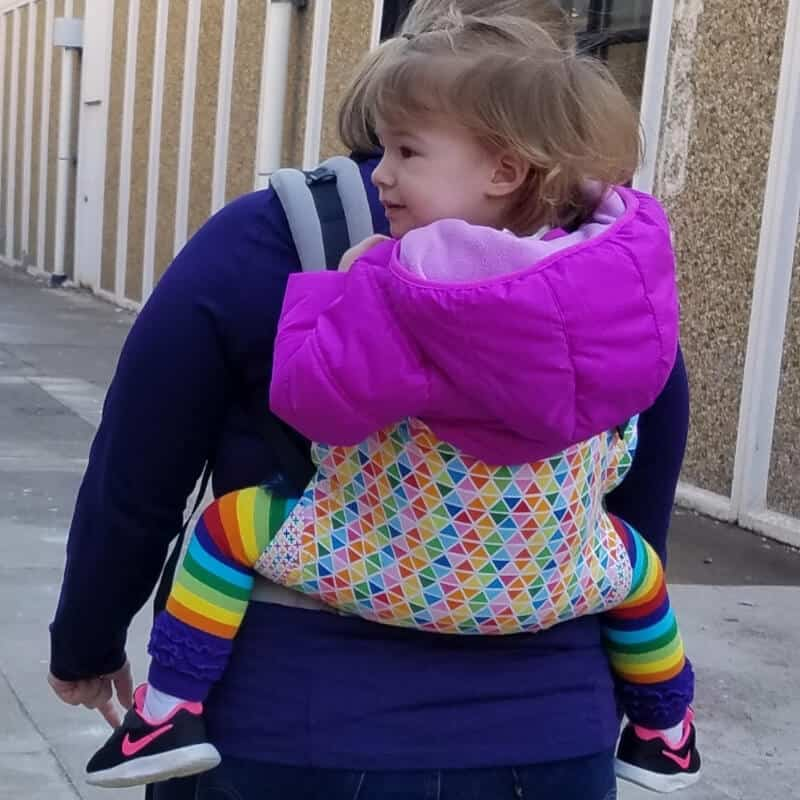 Toddler girl in standard Tula baby carrier, in Confetti Pop print.